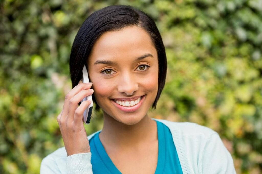 a happy young lady using her phone